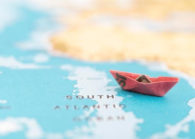 Kleines boot auf weltkarte