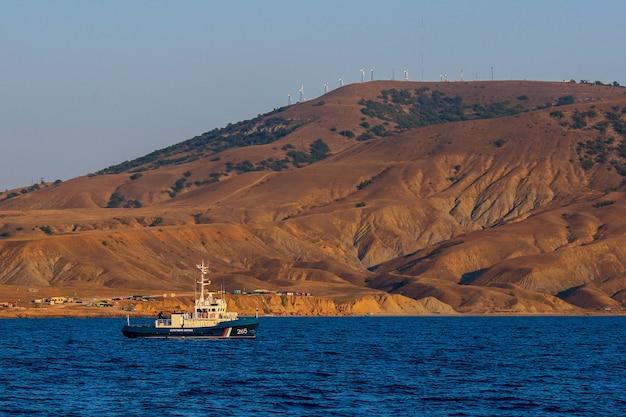 Kleines boot, das auf blauem meer bei sonnenuntergang mit bergblick segelt.