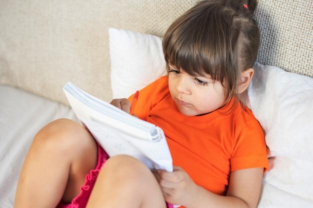 Kleines braunes haarmädchen mit braunen augen. 3 jahre alt. malen mit stift im notizbuch. zu hause auf dem sofa sitzen.