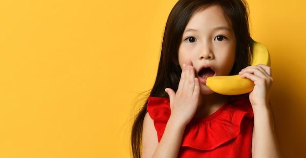 Kleines brünettes asiatisches kind in der roten bluse. sie tut so, als würde sie wie am telefon über bananen sprechen und posiert vor orangefarbenem studiohintergrund. kindheit, früchte, emotionen, werbung. nahaufnahme, platz kopieren