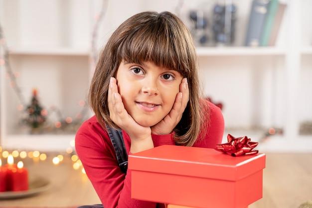 Kleines brünettes mädchen lächelt glücklich zu weihnachten
