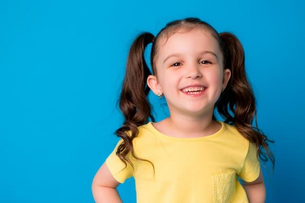 Kleines brunettemädchen auf dem blauen hintergrundlächeln