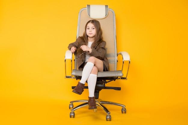 Kleines brunettemädchen im stuhl