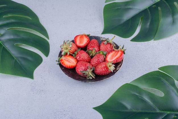 Kleines bündel erdbeeren und dekorative blätter auf marmorhintergrund.