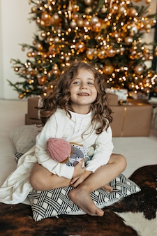 Kleines charmantes mädchen, das auf kissen mit spielzeug über weihnachtsbaum, neujahrsstimmung, weihnachtsfeier sitzt