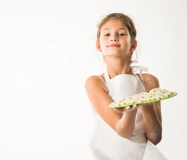Kleines charmantes mädchen, das ein brett mit keksen hält