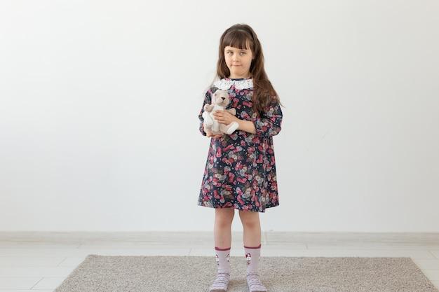 Kleines charmantes mädchen in einem blumenkleid umarmt sanft ihren lieblingsspielzeughasen, der auf einem weiß steht