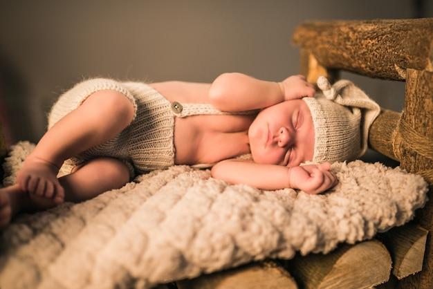 Kleines charmantes neugeborenes in strickanzug und mütze schläft auf einem weichen wollplaid