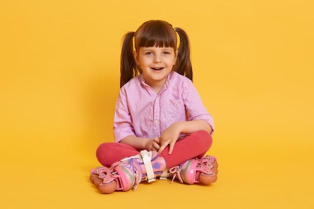 Kleines charmantes süßes mädchen mit rollschuhen, die auf boden mit gekreuzten beinen sitzen