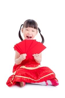 Kleines chinesisches mädchen im roten farbtraditionellen kleid, das rotes paketgeld hält