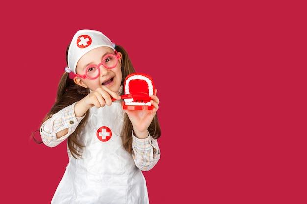 Kleines cooles doktorzahnarztmädchen in einem medizinischen anzug