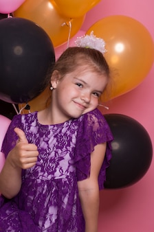 Kleines dunkelhaariges mädchen mit bunten ballonen