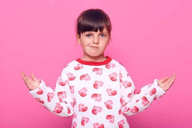 Kleines dunkelhaariges weibliches kind, das mit sich ausbreitenden händen beiseite wirft, kamera mit stirnrunzelndem gesicht betrachtet, lässige kleidung tragend, über rosa wand isoliert.