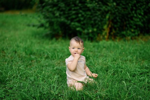 Kleines einjähriges mädchen sitzt im gras.