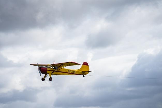 Kleines einmotoriges flugzeug, das im englischen bewölkten himmel fliegt