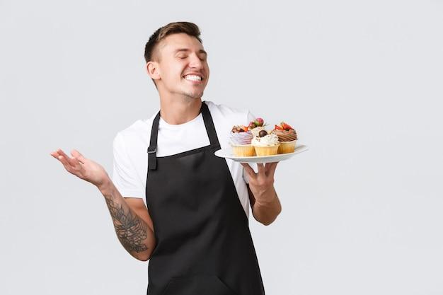 Kleines einzelhandelsgeschäft, cafés und bäckereikonzept, das einen glücklichen, gutaussehenden barista-kellner im laden lächelt...
