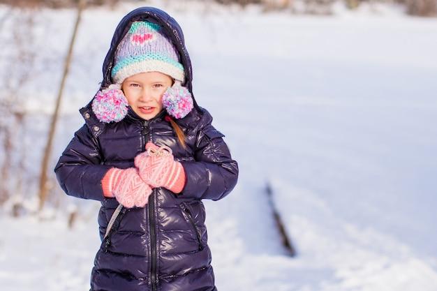 Kleines entzückendes glückliches mädchen, das sonnigen wintertag des schnees genießt