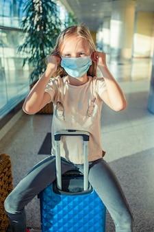 Kleines entzückendes kind mit chirurgischem maskengesichtsschutz am internationalen flughafen. schutz gegen coronavirus und gripp