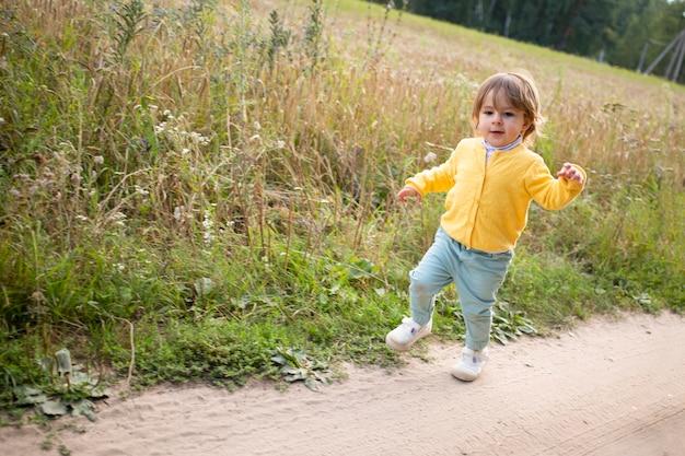 Kleines entzückendes kleinkind, das auf der landstraße im sommerfeld spaziert. kinderurlaub auf dem land