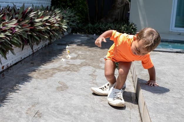 Kleines entzückendes kleinkindbaby, das erwachsene turnschuhe anprobiert.