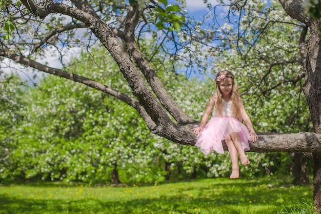 Kleines entzückendes mädchen, das auf blühendem apfelbaum sitzt