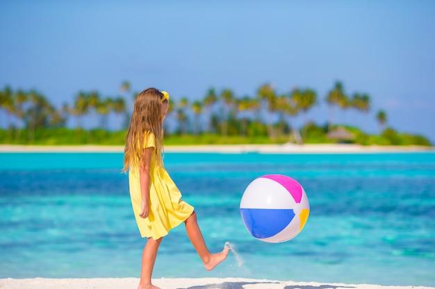 Kleines entzückendes mädchen, das auf strand mit ball spielt