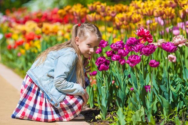 Kleines entzückendes mädchen, das bunte tulpen am sommertag riecht