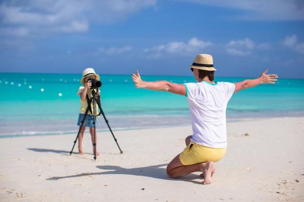 Kleines entzückendes mädchen, das foto von ihrem jungen vater am exotischen strand macht