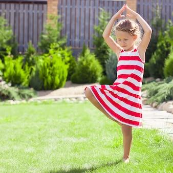 Kleines entzückendes mädchen, das in einer yogahaltung auf einem bein steht