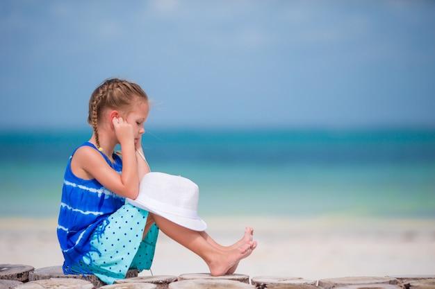 Kleines entzückendes mädchen, das musik auf kopfhörern auf dem strand hört