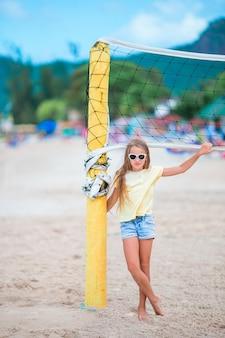 Kleines entzückendes mädchen, das strandvolleyball mit ball spielt. sportliches kind genießen strandspiel draußen