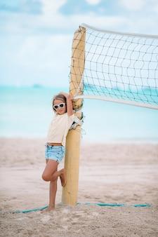 Kleines entzückendes mädchen, das voleyball auf strand mit ball spielt.