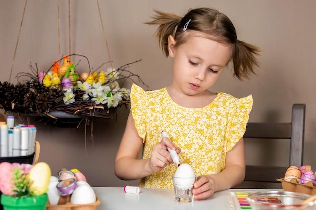 Kleines entzückendes mädchen im gelben kleid, das ostereier mit pinsel und aquarellen malt
