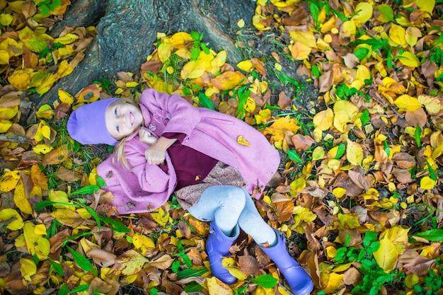 Kleines entzückendes mädchen im herbstpark am sonnigen falltag