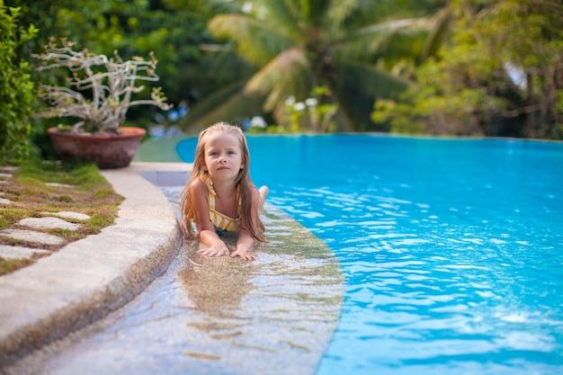 Kleines entzückendes mädchen im swimmingpool betrachtet kamera
