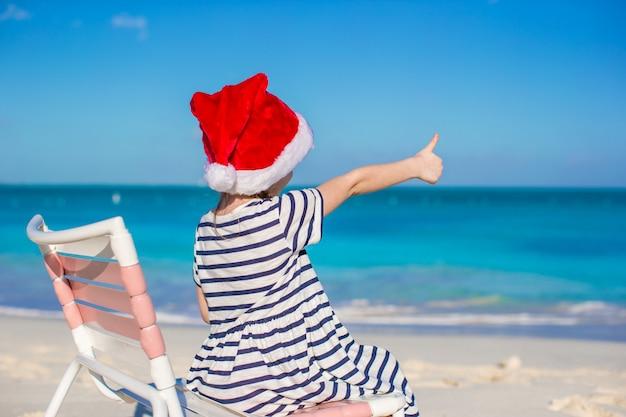 Kleines entzückendes mädchen in roter weihnachtsmütze auf strandstuhl