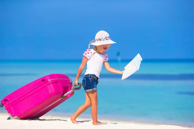 Kleines entzückendes mädchen mit großem koffer auf tropischem weißem strand