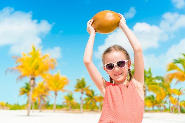Kleines entzückendes mädchen mit großer kokosnuss am strand
