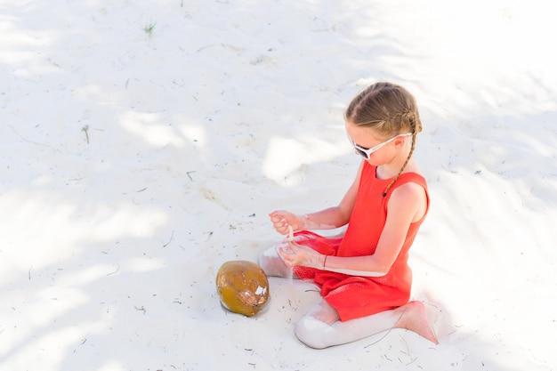 Kleines entzückendes mädchen mit großer kokosnuss auf weißem sandigem strand