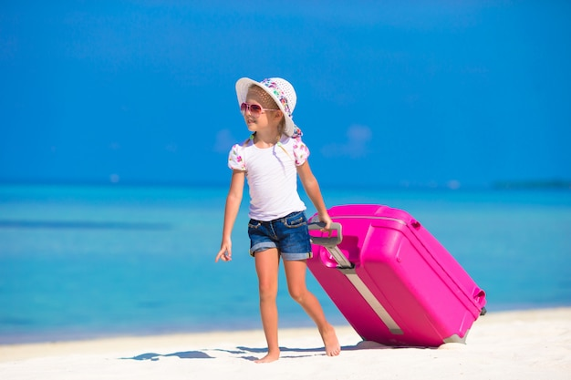 Kleines entzückendes mädchen mit großer tasche auf weißem strand