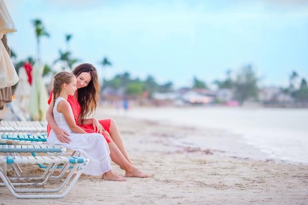 Kleines entzückendes mädchen und junge mutter am tropischen strand