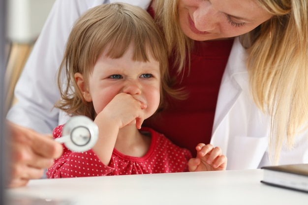 Kleines erschrockenes kind an der doktoraufnahme machen insulinschuss.