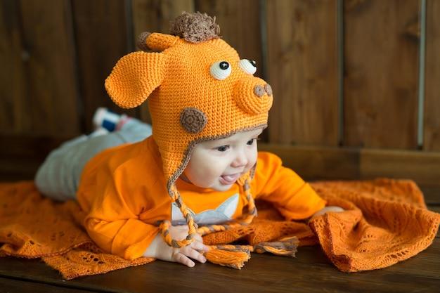Kleines europäisches baby in leuchtend orangefarbenen kleidern