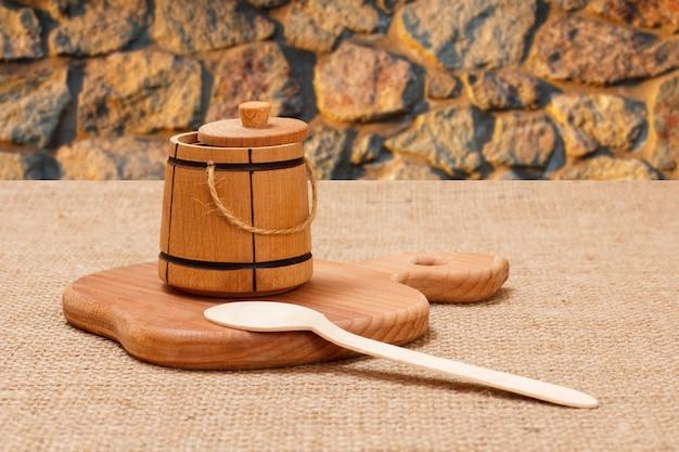 Kleines fass zum aufbewahren von salz oder gewürzen auf einem holzbrett mit steinhintergrund.