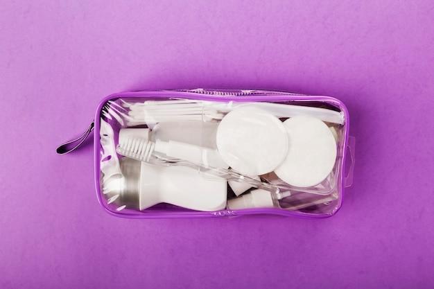 Kleines flaschenset für die reise, in transparenter kosmetiktasche auf lila
