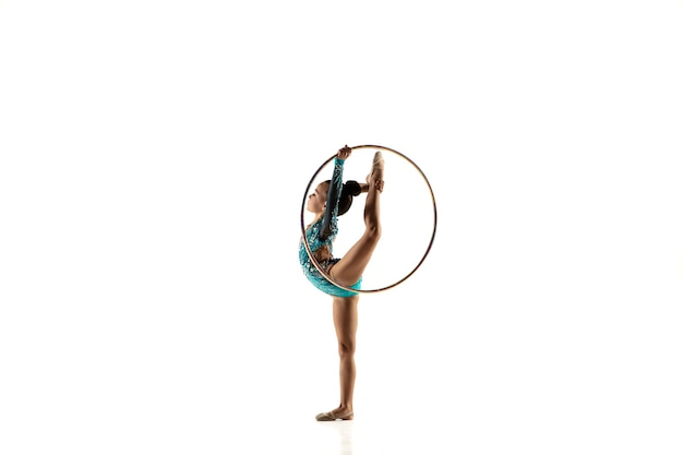 Kleines flexibles mädchen lokalisiert auf weiß. kleines weibliches modell als rhythmische gymnastikkünstlerin im hellen trikot. Kostenlose Fotos