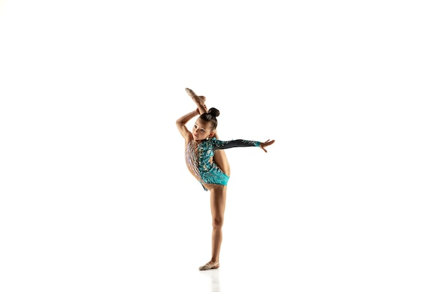 Kleines flexibles mädchen lokalisiert auf weiß. kleines weibliches modell als rhythmische gymnastikkünstlerin im hellen trikot.