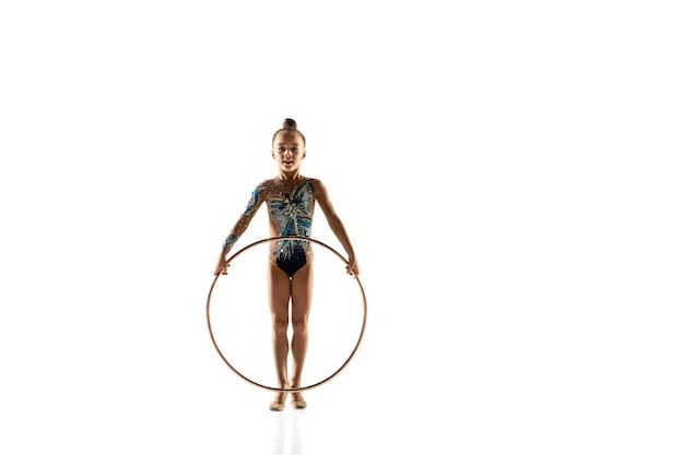 Kleines flexibles mädchen lokalisiert auf weißer wand. kleines weibliches modell als rhythmische gymnastikkünstlerin im hellen trikot. anmut in bewegung, action und sport. übungen mit dem reifen machen.