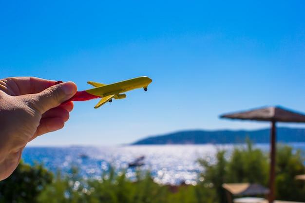 Kleines flugzeug in der weiblichen hand auf hintergrund des blauen himmels