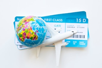 Kleines Flugzeug mit Tickets und Globus